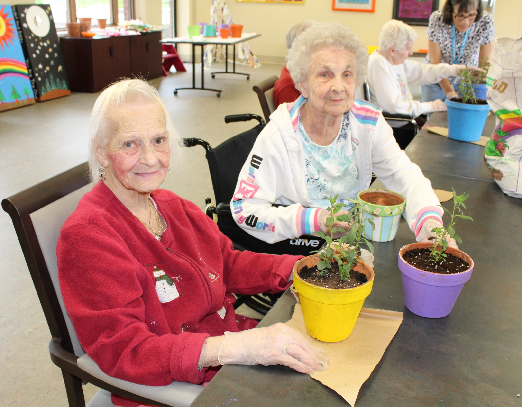 Assisted Living residents planted flowers in colorful pots for the Seasons Studio!